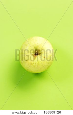 Green apple on green background.Useful as a food background