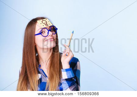 Woman confused thinking seeks solution paper card with light idea bulb on her head. Girl is trying to create a new idea for some business project or case study studio shot on blue