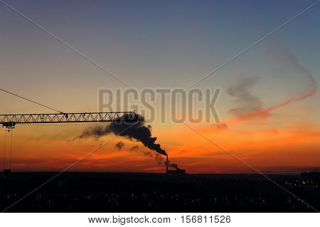 The smoke from thermal power plants and a crane at sunset