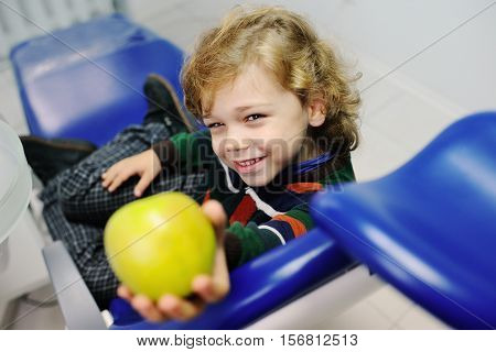small child with curly hair in a striped sweater, sitting in the dental chair and holding a green apple. Examination of the teeth at the dentist.