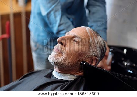 Time to think. Close up of old bearded man sitting and holding his head in special sink in barber shop during washing procedure.