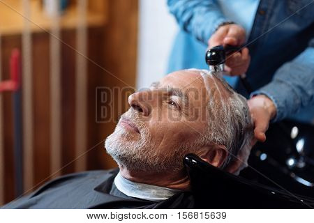 Scrupulous work. Close up of senior bearded man with grey hair holding his head in special sink in barber shop while washing procedure.
