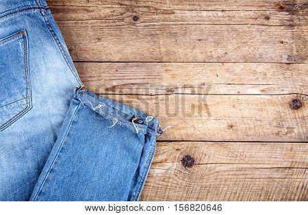 Stylish Jeans Folded On A Wooden Background. Clothing, Fashion, Lifestyle.