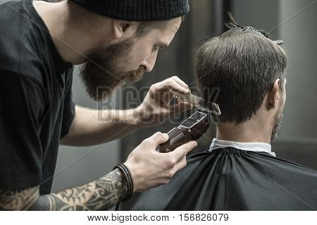 Incomparable barber with a beard and a tattoo is cutting the hair of his client in the black cape in the barbershop. He is using a cutting comb and a hair clipper. Hairdresser dressed in black wear.