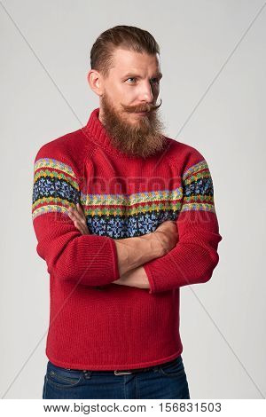 Serious confident bearded hipster man in woolen sweater standing with folded hands and looking away out of frame, studio portrait over grey background