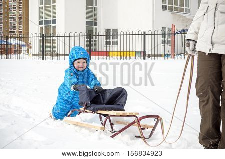 Young Mother And Little Boy Enjoying Sleigh Ride. Child Sledding. Toddler Kid Riding Sledge. Childre