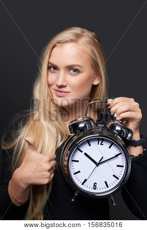 Happy woman with big alarm clock gesturing thumb up sign over grey background