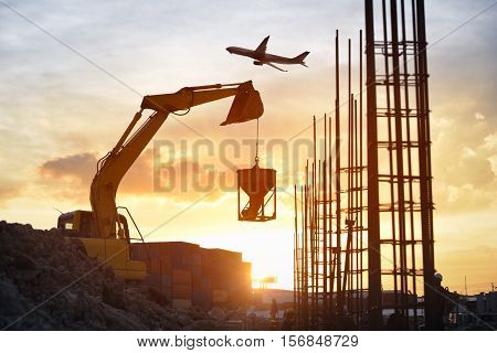 Silhouette photo of excavator lift-up the concrete buckets for casting to foundation of building concrete., overtime work on sunset in construction site