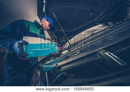 Refilling Car Windshield Washer Fluid by Professional Car Service Technician.