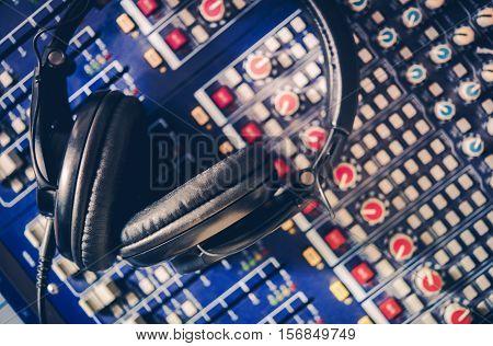 Pro Headphones on the Sound Mixing Table. Audio Mixer. Recording Studio and Audio Broadcast Theme.