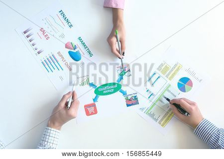 Top View of Business Meeting with Paper Charts on White Desk Hands of People discussing pointing with pens