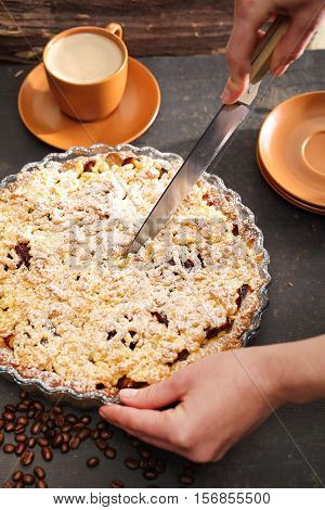 Cake with plums. Homemade pastries. Tart on flaky pastry with plums and powdered sugar