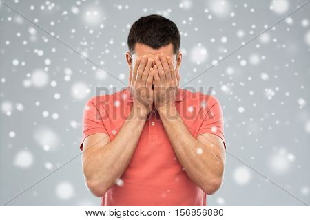 people, fear, emotions, winter and stress concept - man in white t-shirt covering his face with hands over snow on gray background