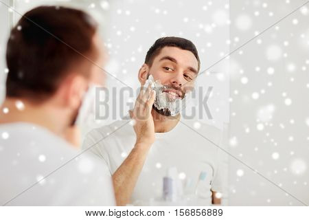 beauty, hygiene, shaving, grooming and people concept - smiling young man looking to mirror and applying shaving foam to face at home bathroom over snow