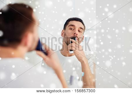 beauty, shaving, grooming and people concept - young man looking to mirror and shaving beard and mustache with trimmer or electric shaver at home bathroom over snow