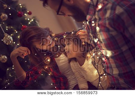 Beautiful young family enjoying their holiday time together decorating Christmas tree arranging the christmas lights and having fun