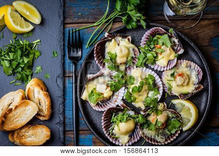 Seafood. Shellfish. Baked scallops on black plate with lemon, cilantro, bread and white wine on wooden blue background. Top view