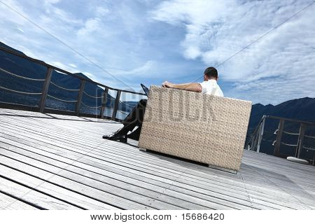businessman relaxing outdoors sitting by the lake