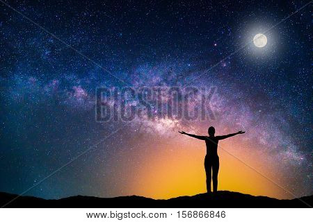 Landscape with Milky way galaxy. Night sky with stars moon and silhouette happy woman on the mountain.