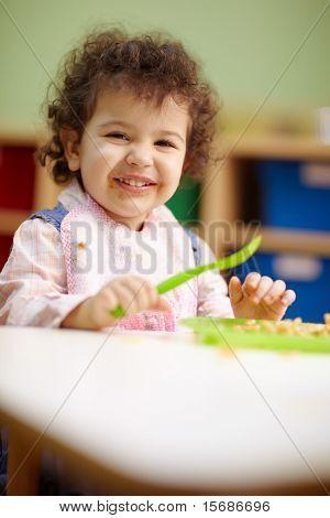 Little Girl Eating Lunch In Kindergarten