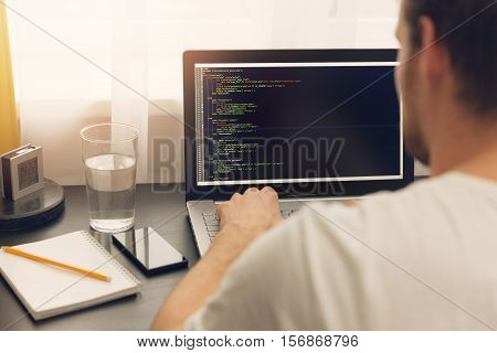 website programmer working on laptop at office