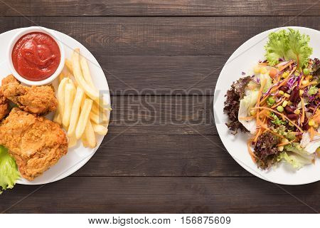 Fresh Salad And Fried Chicken And French Fries On The Wooden Background. Contrasting Food