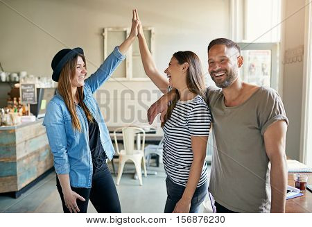 Two women putting up high fives with bearded handsome male friend standing next to them in coffee house