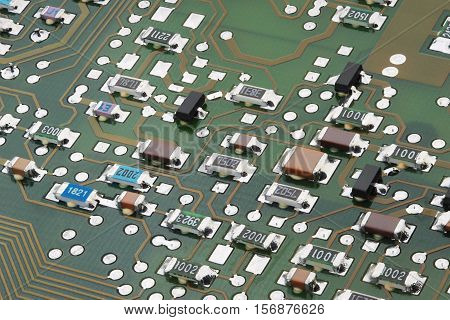 Surface-mount components on electronic circuit board close-up.