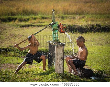 Two young boy rocking groundwater bathe in the hot days Countryside Thailand.
