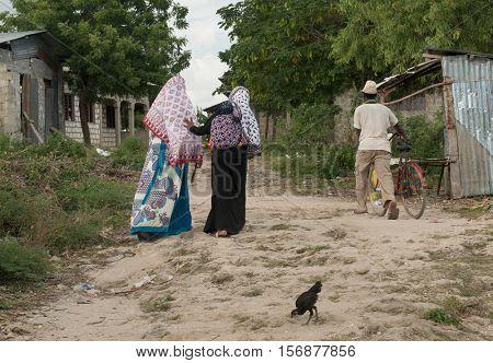 ZANZIBAR, TANZANIYA- JULY 13: people passing by in poor village on July 13, 2016 in Zanzibar