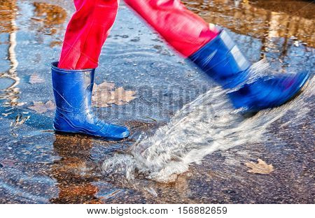 girl in blue boots and red pants standing in a puddle of water splashes with fallen yellow leaves on autuman day closeup