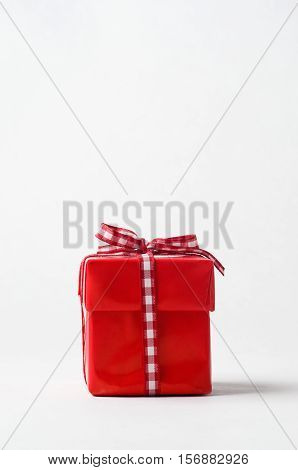 Eye level shot of a square Christmas gift box with lid wrapped in red paper and tied to top with gingham ribbon bow. Copy space above.