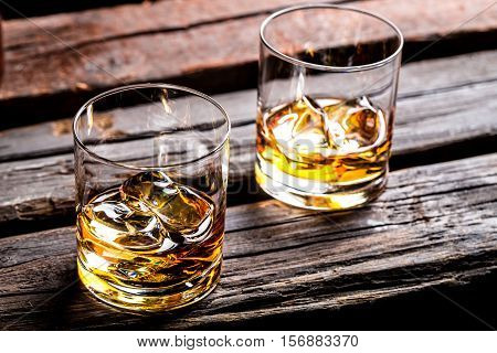 Two Glasses With Ice And Whiskey On Black Background