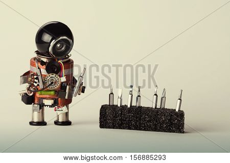 Robot with screwdriver set. Fun toy repair man character black helmet head and hardware instrument. Macro view shallow depth of field gradient background copy space.