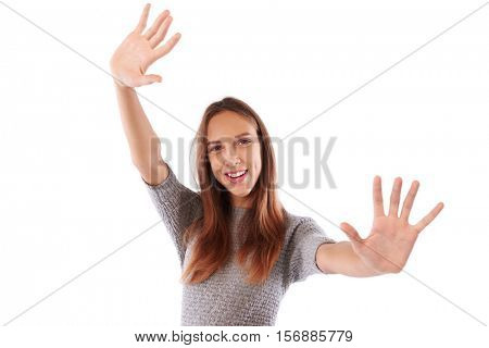 Close-up shot of elated smiling girl showing two open palms at the camera while standing over the white background