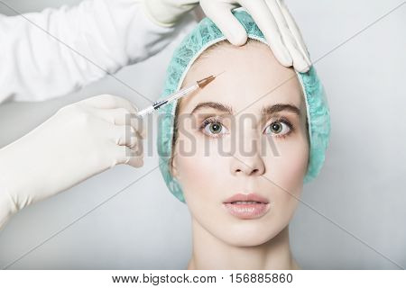 Doctor aesthetician makes hyaluronic acid beauty injections in the forehead of female patient in a green medical cap