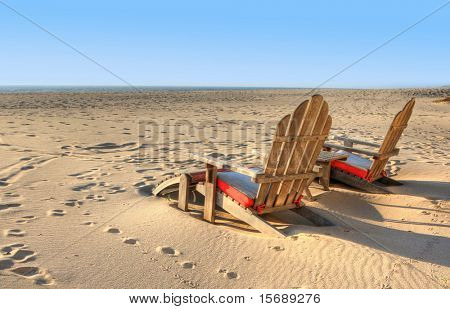 Two beach chairs sitting in the sand