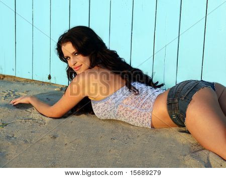 Beautiful brunette model laying next to a wall at the beach
