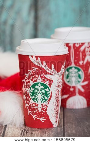 DALLAS TX - NOVEMBER 15 2016: A cup of Starbucks popular holiday beverage served in the new 2016 designed red holiday cup. Displayed with Christmas hats on wooden rustic table.