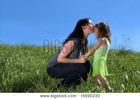 Madre dando un beso a su hija en un prado