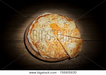 Cheese Italian pizza with a whole egg yolk in the middle and cut pieces served on a wooden plate at hard light studio