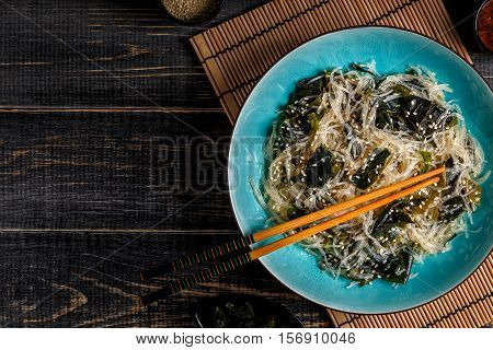 Funchoza salad with wakame on dark background top view.