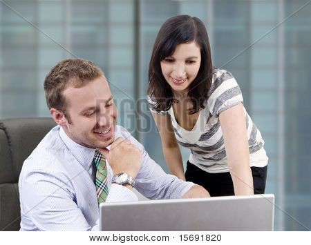 Male business man showing a female coworker something on the computer