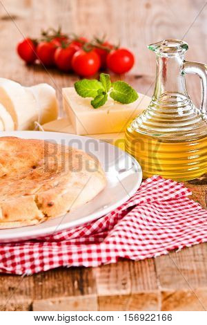 Cheese focaccia bread with ingredients on white dish.