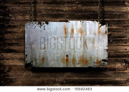 A metal banner held with chains on a grungy wood background - room for copy on the banner
