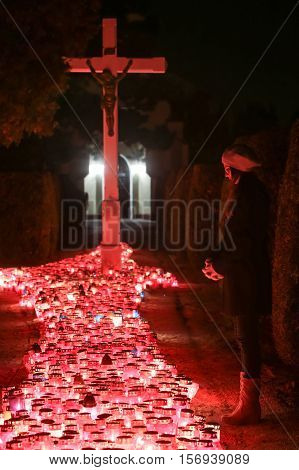 A night view of a woman praying in front of the cross with a large group of burning lampions on the floor at cemetery in Velika Gorica Croatia.