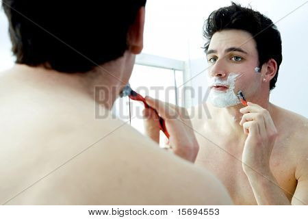 Young man shaving in the mirror