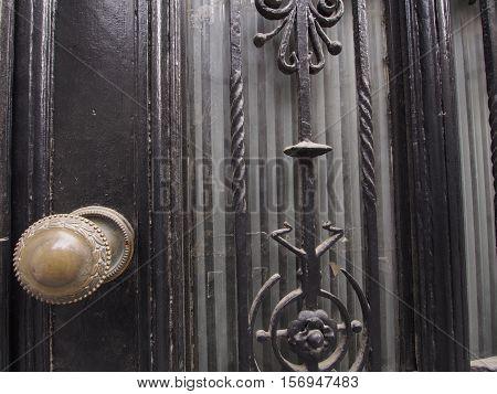 Ornate brass doorknob with embossing on black door