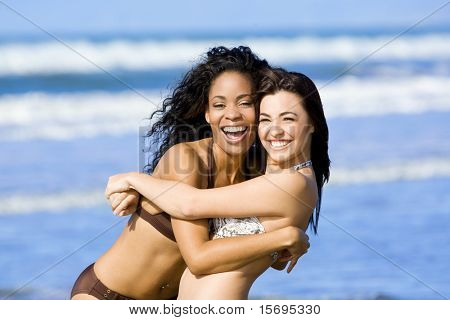 Two happy diverse friends playing at the beach