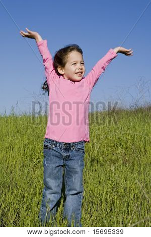 Cute little girl raising her arms in the spring sun